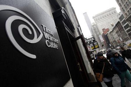 Pedestrians walk past the Time Warner Cable headquarters in New York