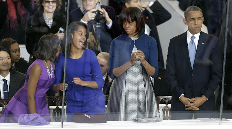 President Barack Obama, right, and first lady Michelle Obama watch the Inaugural parade down Pennsylvania Avenue as their daughters, Sasha, left, and Malia, second from left, dance in the presidential box near the White House, Monday, Jan. 21, 2013, in Washington. Thousands  marched during the 57th Presidential Inauguration parade after the ceremonial swearing-in of President Barack Obama. (AP Photo/Gerald Herbert)