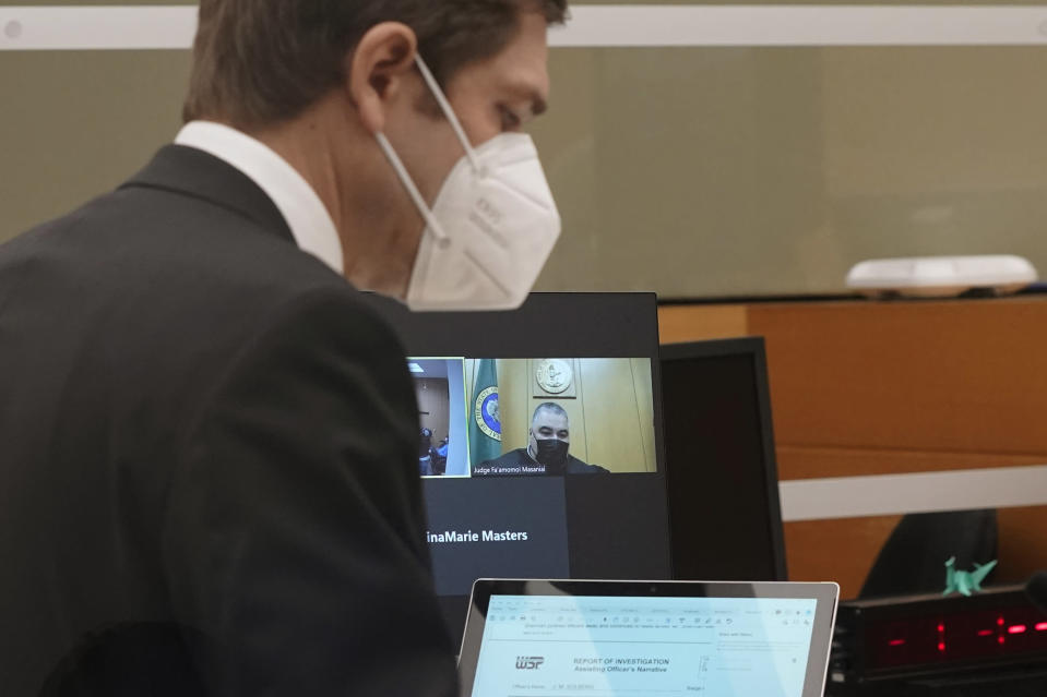 Cooper Offenbecher, left, an attorney for NFL football cornerback Richard Sherman, appears in a district court hearing at the King County Correctional Facility, Thursday, July 15, 2021, in Seattle as Judge Fa'amomoi Masaniai appears on a video link. Sherman, who has played for the Seattle Seahawks and the San Francisco 49ers, was arrested early Wednesday after police said he crashed his car in a construction zone and then tried to break into his in-laws' home in the Seattle suburb of Redmond, Wash. (AP Photo/Ted S. Warren)