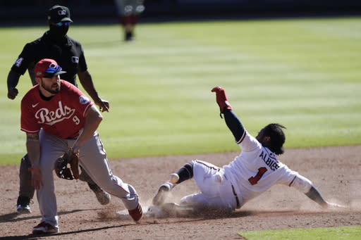 Atlanta Braves' Ozzie Albies (1) steals second base as Cincinnati Reds second baseman Mike Moustakas (9) looks on in 12th inning during Game 1 of a National League wild-card baseball series, Wednesday, Sept. 30, 2020, in Atlanta. (AP Photo/John Bazemore)