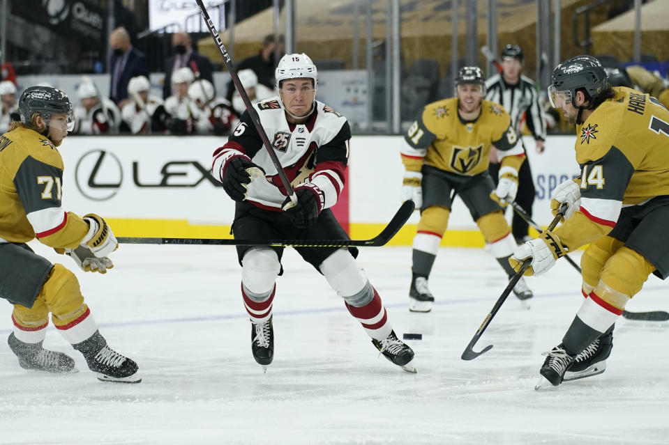 Arizona Coyotes left wing John Hayden (15) skates up the ice against Vegas Golden Knights center William Karlsson (71) and defenseman Nicolas Hague (14) during the third period of an NHL hockey game Wednesday, Jan. 20, 2021, in Las Vegas. (AP Photo/John Locher)