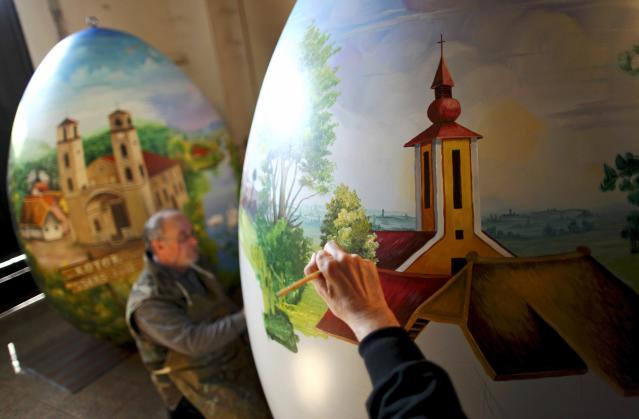 Local artists paint a two-meter-high Easter egg in the traditional naive art style in the northern Croatian town of Koprivnica March 13, 2014. The project, which started several years ago, involves painters decorating two-metre-tall polyester eggs, which are then sent to cities in the country and abroad to be displayed in public squares in time for Easter festivities. This year, three giant eggs will be painted and sent to Montenegro, Paris and Riga, the 2014 European Capital of Culture. Picture taken March 13, 2014. REUTERS/Antonio Bronic (CROATIA - Tags: SOCIETY RELIGION TPX IMAGES OF THE DAY)