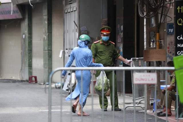 A woman leaves the food shopping for her relatives at the barricaded entrance to the residence of a suspected COVID-19 case in Hanoi, Vietnam on Wednesday, July 29, 2020. Vietnam intensifies protective measures as the number of locally transmissions, starting at a hospital in the popular beach city of Da Nang, keeps increasing since the weekend. (AP Photo/Hau Dinh)