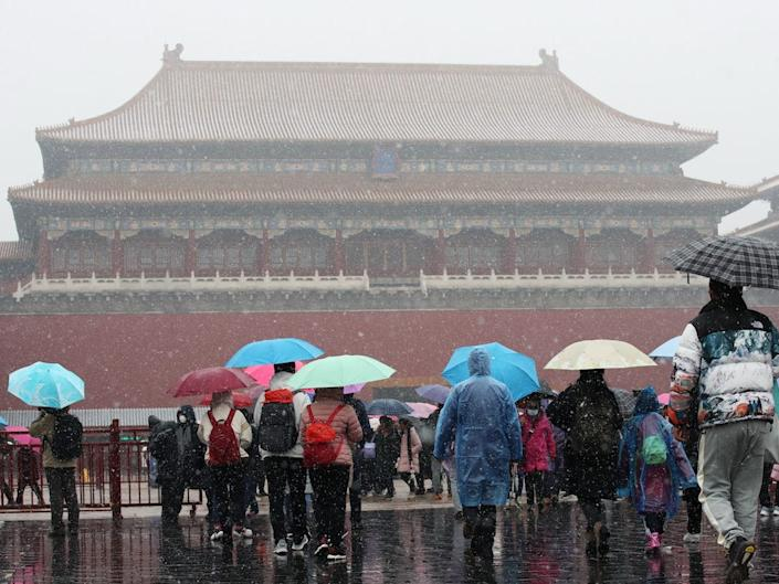 People holding umbrellas visit the Forbidden City during the first snow of the season on November 21, 2020