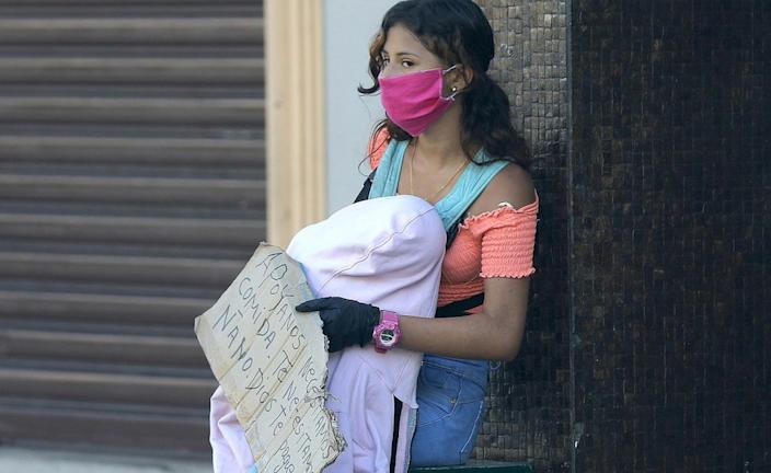 A woman with her baby begs for help as the country suffers economic pain from the health crisis