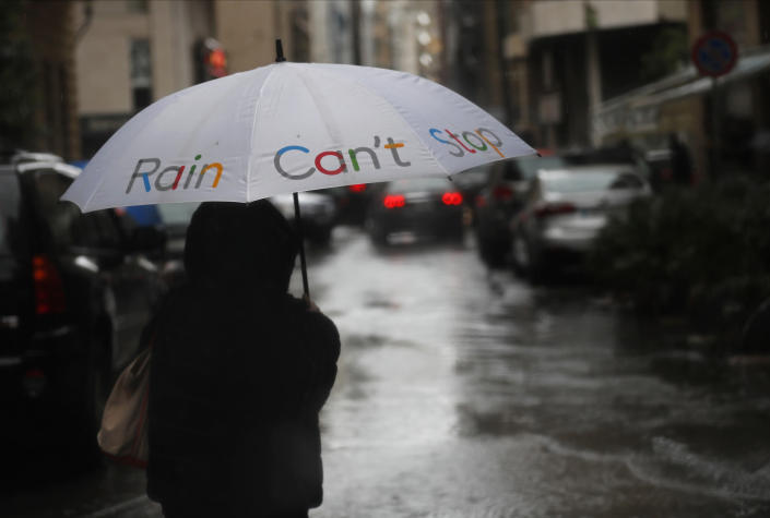 A woman holds her umbrella as she crosses a street, in Beirut, Lebanon, Wednesday, Feb. 17, 2021. Breaking a warm spell, Storm Joyce that hit Lebanon brought heavy rainfall, a sharp drop in temperatures and the heaviest snow fall in Lebanon this year. (AP Photo/Hussein Malla)