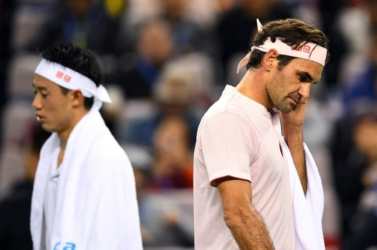 Roger Federer's (L) Shanghai title defence belatedly caught fire with victory over Kei Nishikori (L) of Japan