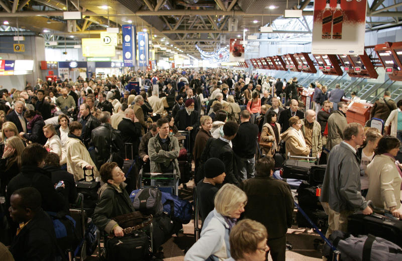 Passengers queue in Terminal 4 at Heathrow airport in west London December 22, 2006. Thousands of travellers struggling to get home for Christmas faced another day of chaos and frustration on Friday as London's Heathrow airport was blanketed in fog. REUTERS/Stephen Hird (BRITAIN)