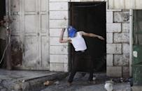 A masked Palestinian protester throws a stone at Israeli troops following a protest against the Israeli police raid on Jerusalem's al-Aqsa mosque on Tuesday, in the occupied West Bank city of Hebron September 18, 2015. REUTERS/Mussa Qawasma