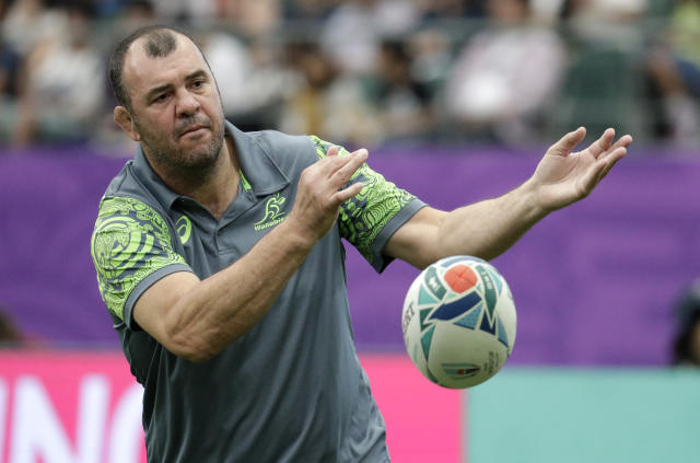 Australian coach Michael Cheika passes the ball as his team warms up ahead of the Rugby World Cup Pool D game at Oita Stadium between Australia and Uruguay in Oita, Japan, Saturday, Oct. 5, 2019. (AP Photo/Aaron Favila)