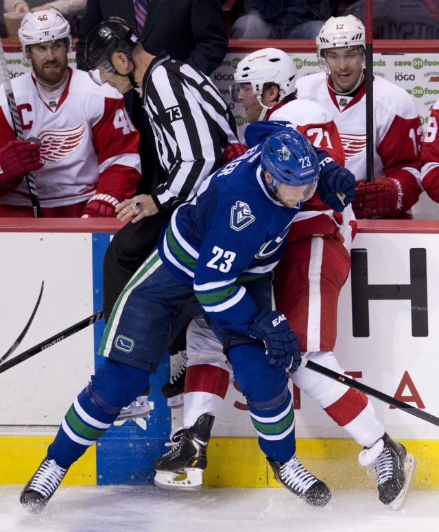 Vancouver Canucks defenseman Alexander Edler (23) puts Detroit Red Wings right wing Daniel Cleary (71) into the boards as linesman Vaughan Rody looks on during the second period of an NHL hockey game in Vancouver, British Columbia, Wednesday, Oct. 30, 2013. (AP Photo/The Canadian Press, Jonathan Hayward)