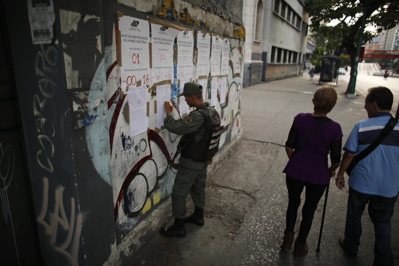 <p>A member of the Bolivarian National Guard looks for an ID number on voters lists at a polling station during the presidential election in Caracas, Venezuela, Sunday, May 20, 2018. Amidst hyperinflation and shortages of food and medicine, President Nicolas Maduro is seeking a second, six-year term in an election that a growing chorus of foreign governments refuse to recognize after key opponents were barred from running. (AP Photo/Ariana Cubillos) </p>