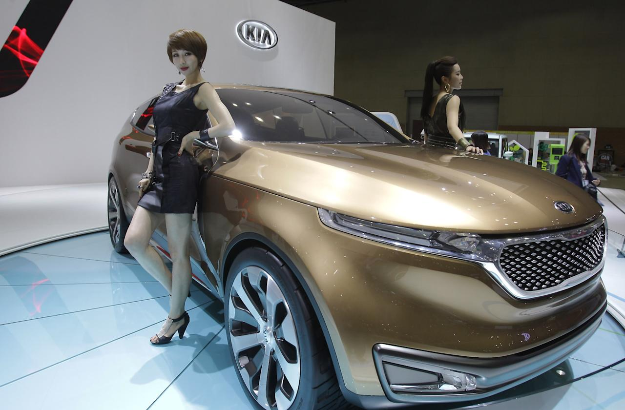 GOYANG, SOUTH KOREA - MARCH 28:  Models pose next to a KIA Eco Hybrid at the Seoul Motor Show 2013 on March 28, 2013 in Goyang, South Korea. The Seoul Motor Show 2013 will be held in March 29-April 7, featuring state-of-the-art technologies and concept cars from global automakers. The show is its ninth since the first one was held in 1995. About 384 companies from 14 countries, including auto parts manufacturers and tire makers, will set up booths to showcase trends in their respective industries, and to promote their latest products during the show.  (Photo by Chung Sung-Jun/Getty Images)