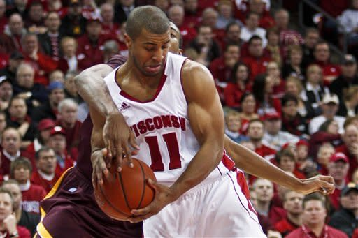 Wisconsin's Jordan Taylor (11) keeps the ball away from Minnesota's Austin Hollins during the first half of an NCAA college basketball game Tuesday, Feb. 28, 2012, in Madison, Wis. (AP Photo/Andy Manis)