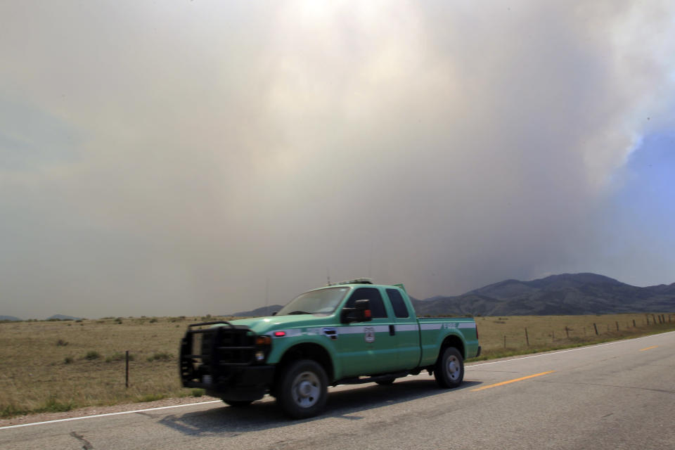 A U.S. Forest Service truck heads down Larimer County Road 74W as a wildfire continues to burn near Livermore, Colo., on Saturday, June 23, 2012. Authorities sent out 992 evacuation notices Friday due to the wildfire burning on more than 100 square miles in northern Colorado as winds pick up. (AP Photo/David Zalubowski)