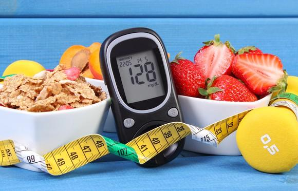 Diabetes glucose monitor with healthy foods, a barbell, and a tape measure.