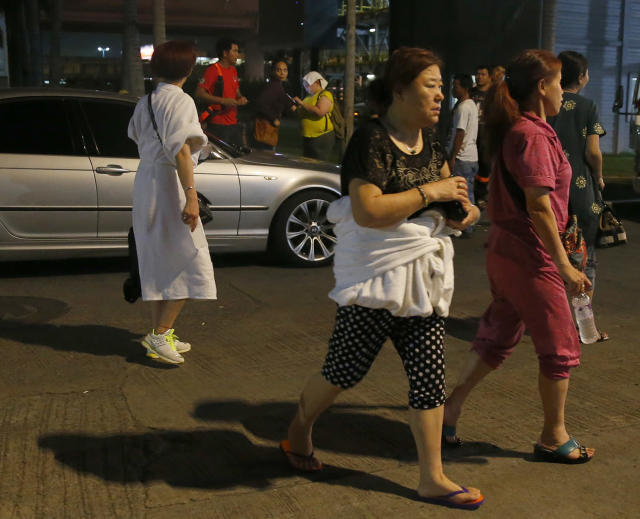 <p>Hotel guests, one with a robe wrapped around her body, walk away from the Resorts World Manila complex early Friday, June 2, 2017 in suburban Pasay city southeast of Manila, Philippines. (Photo: Bullit Marquez/AP) </p>