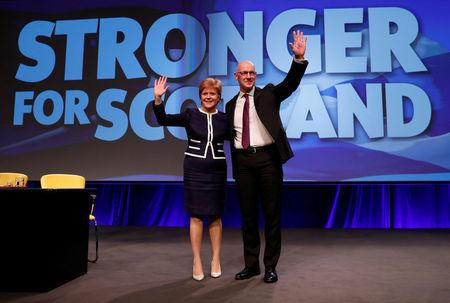 Nicola Sturgeon, First Minister of Scotland, and Deputy First Minister John Swinney wave at the Scottish National Party (SNP)'s party conference in Aberdeen, Scotland, Britain March 17, 2017. REUTERS/Russell Cheyne