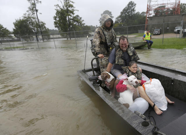 <p>John and Cathy Cservek hold their dogs Lacy and Iggy while being rescued from their home as floodwaters from Tropical Storm Harvey rise, Aug. 28, 2017, in Spring, Texas. (Photo: David J. Phillip/AP) </p>