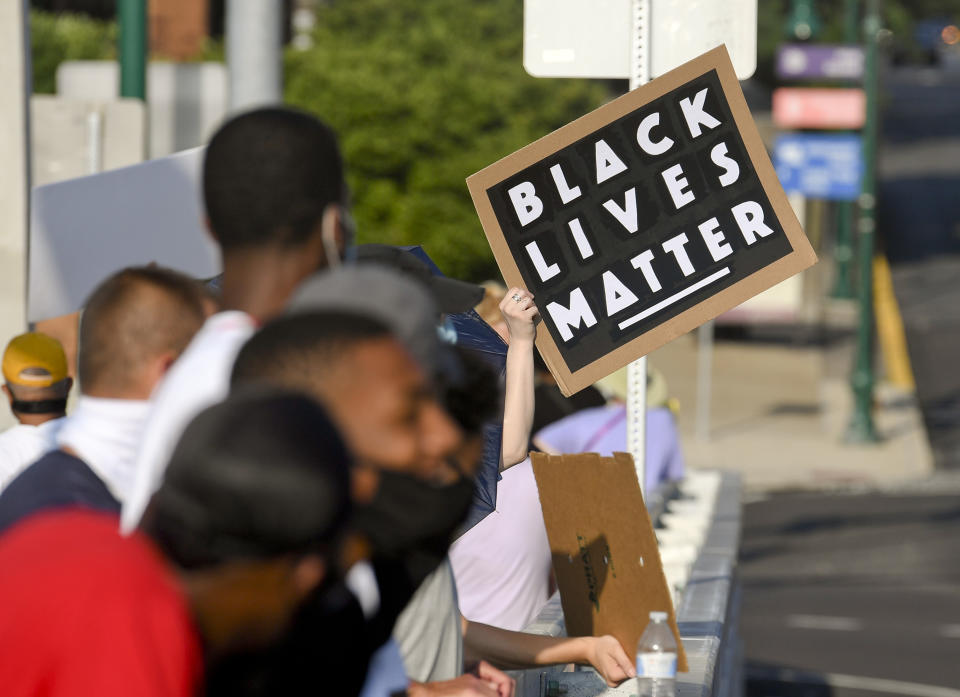 """Reading, PA - July 9: A protester holds a sign that reads """"Black Lives Matter"""" along with other protesters on the bridge holding signs during the Peaceful Stand at the Penn Street Bridge in Reading Thursday evening July 9, 2020. The event was organized by Muhlenberg boys basketball coach and retired NBA player Tyrone Nesby and Friends, and is intended to take a stand against systemic racism and police brutality. This is the third time the Peaceful Stand has been held. Most of the protesters wore face masks as a precaution against the spread of coronavirus / COVID-19. (Photo by Ben Hasty/MediaNews Group/Reading Eagle via Getty Images)"""