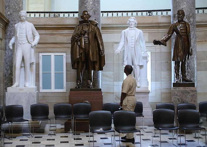 US Navy Lt. William Edmund Newsome looks at a bronze statue of Confederate president Jefferson Davis (2ndL) that stands inside of Statuary Hall at the US Capitol June 24, 2015 in Washington, DC. (Photo by Mark Wilson/Getty Images)