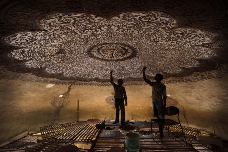 In this June 7, 2013, photo, Indian laborers work to renovate the Neela Gumbad, or Blue Tomb, as part of a project for the creation of a mammoth, iconic park that would rival New York's Central Park as a refuge from urban chaos in New Delhi. To create that park would require the merger of a string of adjoining gardens, heritage areas and a zoo administered by different government agencies, an incredibly complicated task in a land where bureaucratic turfs are fiercely protected. It would be 1,200 acres, considerably larger than Central Park. It would encompass one of the most impressive collections of medieval Islamic monuments, anchored by the grandiose tomb of Emperor Humayun, a 16th Century prototype for the Taj Mahal. (AP Photo/Manish Swarup)