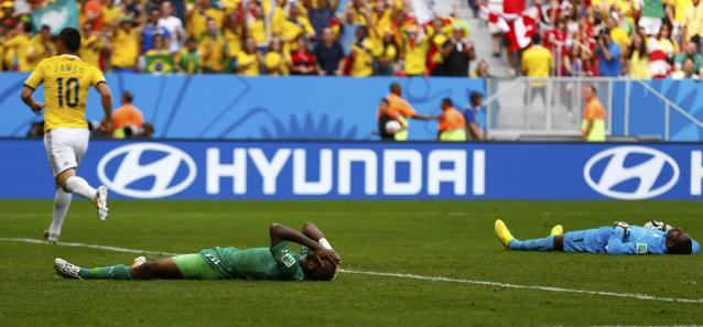 Ivory Coast's Geoffroy Serey Die (C) and his teammate Boubacar Barry (R) react after Colombia's Juan Quintero (unseen) scored his team's second goal during their 2014 World Cup Group C soccer match at the Brasilia national stadium in Brasilia June 19, 2014. REUTERS/Paul Hanna (BRAZIL - Tags: SOCCER SPORT TPX IMAGES OF THE DAY WORLD CUP)