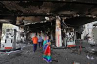 People stand at a damaged fuel station after it was set on fire by a mob in a riot affected area after clashes erupted between people demonstrating for and against a new citizenship law in New Delhi, India, February 26, 2020. REUTERS/Rupak De Chowdhuri
