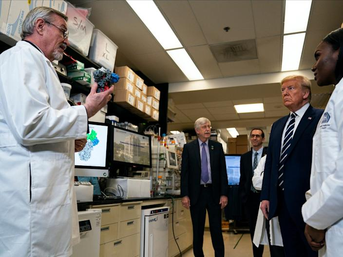 """Deputy Director at the Vaccine Research Center at the National Institutes of Health, Dr. Barney Graham, speaks with President Donald Trump during a tour of the Viral Pathogenesis Laboratory at the National Institutes of Health, Tuesday, March 3, 2020, in Bethesda, Md. <p class=""""copyright"""">Evan Vucci/Associated Press</p>"""