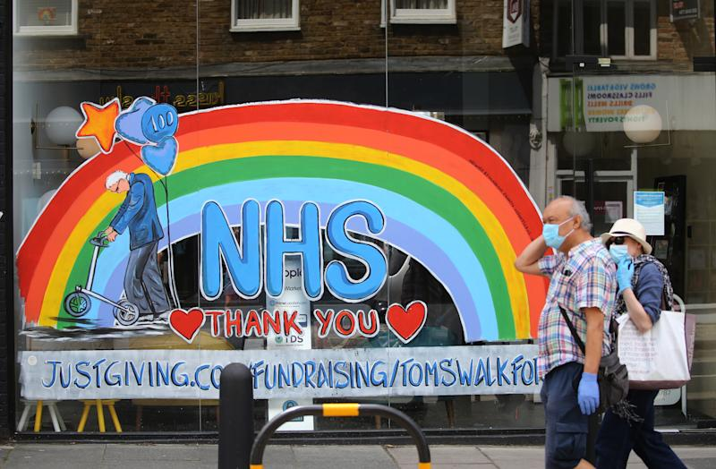A couple wearing protective face mask and gloves walk past a window shop in Crouch End, north London, displaying an artwork depicting Captain Tom and a NHS rainbow to thank key workers for their efforts during the coronavirus pandemic. Picture date: Sunday July 12, 2020.