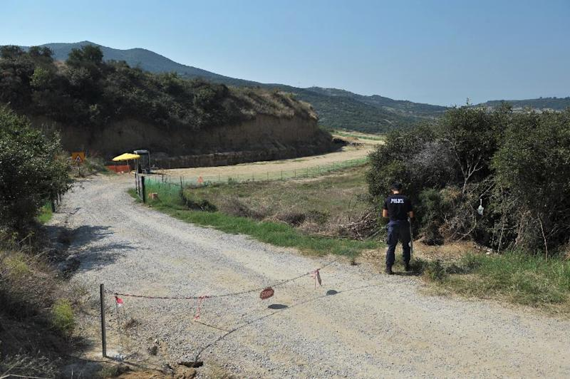 A police officer guards on August 16, 2014 the entrance of the site where archaeologists have unearthed a funeral mound dating from the time of Alexander the Great, in Amphipolis, Northern Greece (AFP Photo/Sakis Mitrolidis)