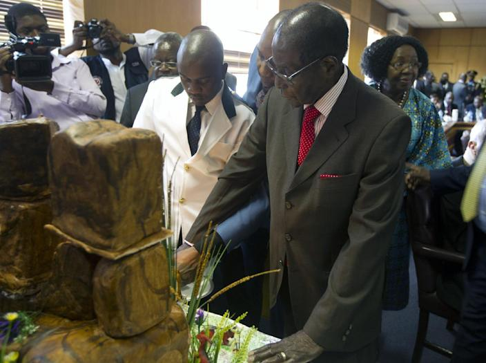 """Zimbabwe's President Robert Mugabe cuts his birthday cake as he marks his 93rd birthday at his offices in Harare, Tuesday, Feb. 21, 2017. Mugabe described his wife Grace, an increasingly political figure, as """"fireworks"""" in an interview marking his 93rd birthday. (AP Photo/Tsvangirayi Mukwazhi)"""