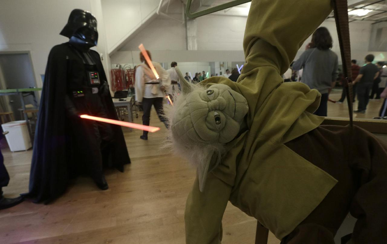 Gary Ripper, dressed as Darth Vader, walks past a Yoda doll during Golden Gate Knights class in San Francisco, Sunday, Feb. 10, 2013. A group of San Francisco Star Wars fans who want to travel to a galaxy not that far away have created a combat choreography class for Jedis-in-training with their weapon of choice: the light saber. (AP Photo/Jeff Chiu)