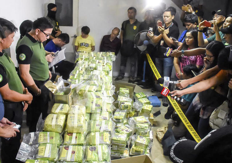 """In this Tuesday, March 19, 2019, photo provided by the Philippine Drug Enforcement Agency, PDEA, Aaron Aquino, second from left, chief of PDEA, looks at more than 160 kilograms (353 pounds) of methamphetamine drugs concealed in tea wrappers following """"buy-bust"""" raids in Alabang township, Muntinlupa city east of Manila, Philippines. It was PDEA's second largest drug haul this year in a sign of how the problem has persisted despite the president's bloody crackdown on illegal drugs. Aquino said Wednesday, March 20, 2019, three Chinese nationals and a Chinese-Filipino man, who works as an interpreter, were arrested, with the drugs concealed in tea wrappers similar to those seized in Malaysia, Thailand and Myanmar and indicated an international drug syndicate was behind the trafficking. (Philippine Drug Enforcement Agency via AP)"""