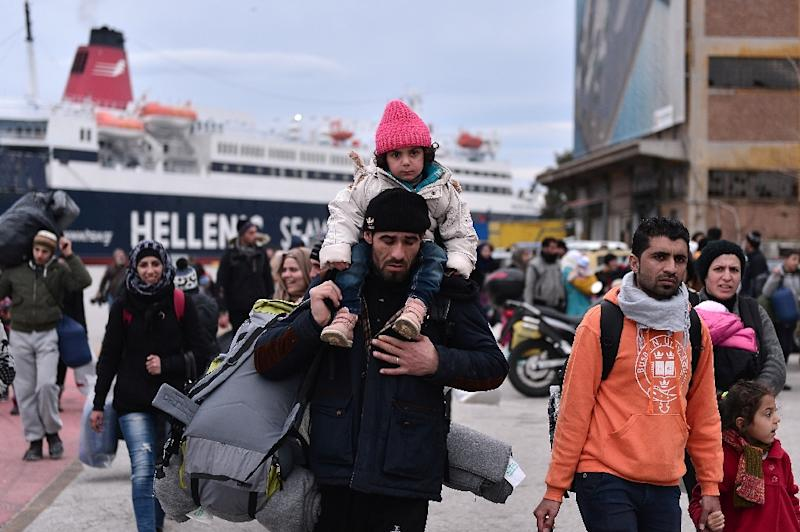 Migrants walk through the port of Piraeus near Athens on their arrival from the island of Lesbos on February 10, 2016 (AFP Photo/Louisa Gouliamaki)