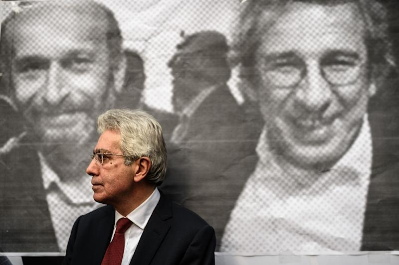A man stands in front of a poster of Can Dundar (left) and Erdem Gul outside the Cumhuriyet Daily's headquarters in Istanbul (AFP Photo/Ozan Kose)