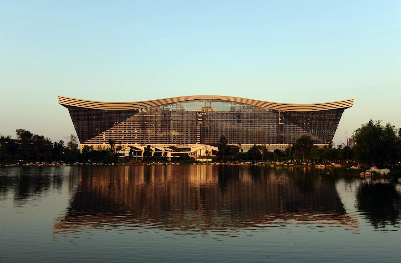 "This picture taken on May 26, 2013 shows the ""New Century Global Centre"" building behind an artificial lake in Chengdu, in southwest China's Sichuan province. The center, claimed by Chinese officials as ""the world's largest standalone structure"", is going to be opened to the public on June 28. The 100m high ""New Century Global Centre"" is a symbol of the spread of China's boom: 500m long and 400m wide, with 1.7 million square metres of floor space - big enough to hold 20 Sydney Opera Houses, according to local authorities.  CHINA OUT     AFP PHOTO"
