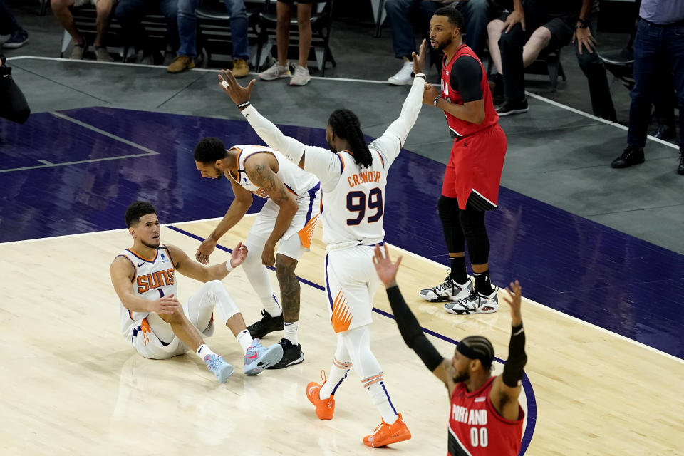 Phoenix Suns guard Devin Booker is helped up by guard Cameron Payne as forward Jae Crowder (99) cheers after being fouled in the final seconds during the second half of an NBA basketball game against the Portland Trail Blazers, Thursday, May 13, 2021, in Phoenix. (AP Photo/Matt York)