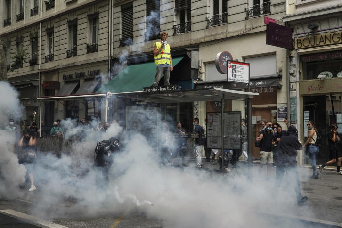 Protestors stand in smoke flares in front of policemen during a demonstration in Lyon, central France, Saturday, July 31, 2021. Demonstrators gathered in several cities in France on Saturday to protest against the COVID-19 pass, which grants vaccinated individuals greater ease of access to venues. (AP Photo/Laurent Cipriani)