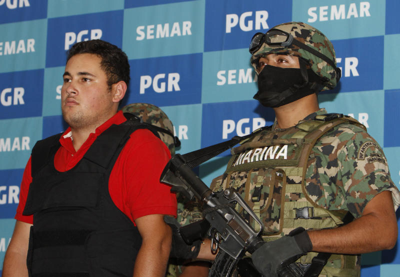 "A Mexican marine escorts Jesus Alfredo Guzman Salazar, left, during his presentation to the media in Mexico City, Thursday, June 21, 2012. Mexican marines detained Jesus Alfredo Guzman Salazar, 26, one of the sons of Mexico's most-wanted drug kingpin, Joaquin ""El Chapo"" Guzman Loera, leader of the powerful Sinaloa cartel. (AP Photo/Marco Ugarte)"