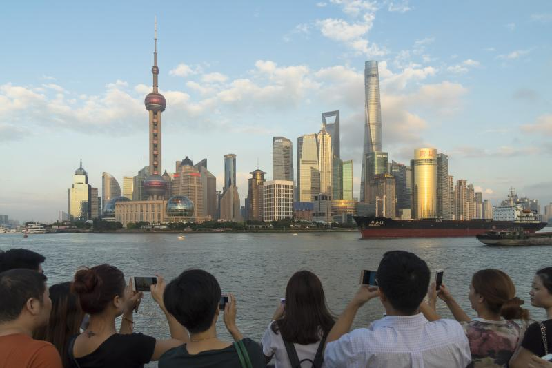 Tourists visiting the promenade on the Shanghai Bund take pictures of the Lujiazui Financial District skyline in Pudong, Shanghai, China, on Sept. 26 2016.