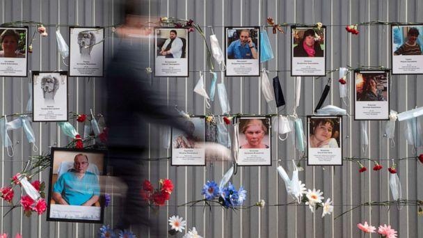 PHOTO: Medical face masks and portraits of St.Petersburg's medical workers who died from coronavirus infection during their work, hang at a unofficial memorial in front of the local health department in St.Petersburg, Russia, May 14, 2020. (Dmitri Lovetsky/AP)