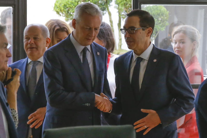 French Finance Minister Bruno Le Maire, left, shakes hands with US Treasury Secretary Steve Mnuchin next to German Finance Minister Olaf Scholz, background left, during a meeting at the G-7 Finance in Chantilly, north of Paris, on Thursday, July 18, 2019. (AP Photo/Michel Euler)