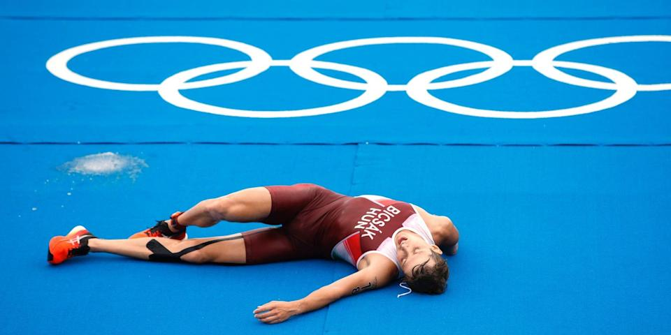 Bence Bicsak of Team Hungary lays on the ground after finishing the Olympic triathlon.
