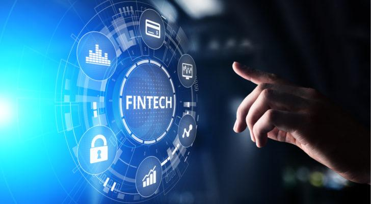 """A hand lingers over a bright blue tech wheel that says """"fintech."""""""