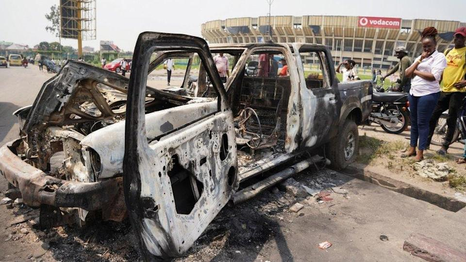 People inspect a burned police car, after two groups of Muslims clashed outside Martyrs' Stadium in Kinshasa, Democratic Republic of Congo - 13 May 2021