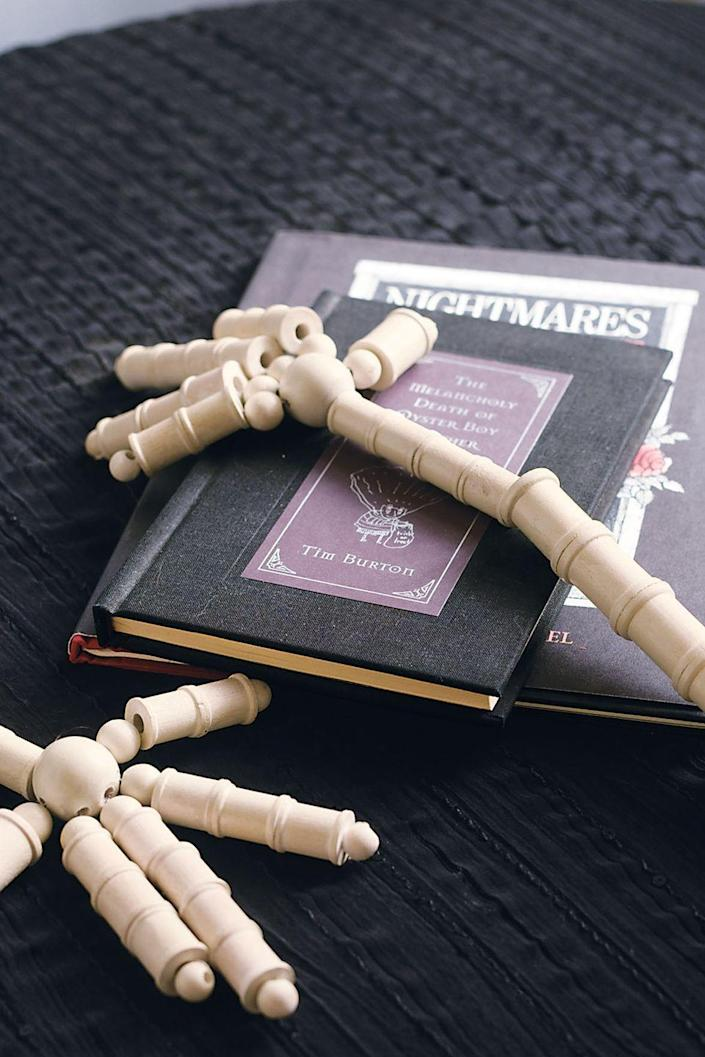 """<p>Give your guests a fright by leaving a pair of these spooky skeleton hands around the house. </p><p><strong><em><a href=""""https://www.womansday.com/home/crafts-projects/how-to/a3073/halloween-crafts-skeleton-hands-21982/"""" rel=""""nofollow noopener"""" target=""""_blank"""" data-ylk=""""slk:Get the Skeleton Hands tutorial"""" class=""""link rapid-noclick-resp"""">Get the Skeleton Hands tutorial</a>. </em></strong></p><p><a class=""""link rapid-noclick-resp"""" href=""""https://www.amazon.com/Chenille-Kraft-3570-Craft-Inches/dp/B0044SD4K2?tag=syn-yahoo-20&ascsubtag=%5Bartid%7C10070.g.2488%5Bsrc%7Cyahoo-us"""" rel=""""nofollow noopener"""" target=""""_blank"""" data-ylk=""""slk:SHOP WOOD SPOOLS"""">SHOP WOOD SPOOLS</a><strong><em><br></em></strong></p>"""