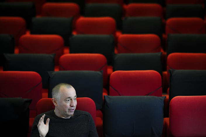 """Romanian investigative journalist Catalin Tolontan speaks during an interview with the Associated Press at the Elvire Popesco cinema in Bucharest, Romania, Monday, April 12, 2021. The Oscar-nominated Romanian documentary film """"Collective"""" follows a group of journalists delving into the state of health care in the eastern European country in the wake of a deadly 2015 nightclub fire that left dozens of burned victims in need of complex treatment. What they revealed was decades of deep-rooted corruption, a heavily politicized system scarily lacking in care. (AP Photo/Andreea Alexandru)"""