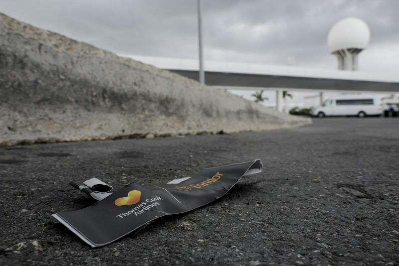 A Thomas Cook luggage tag lays discarded in the street, outside the Cancun airport in Mexico, Monday, Sept. 23, 2019. British tour company Thomas Cook collapsed early Monday after failing to secure emergency funding, leaving tens of thousands of vacationers stranded abroad. (AP Photo/Victor Ruiz)