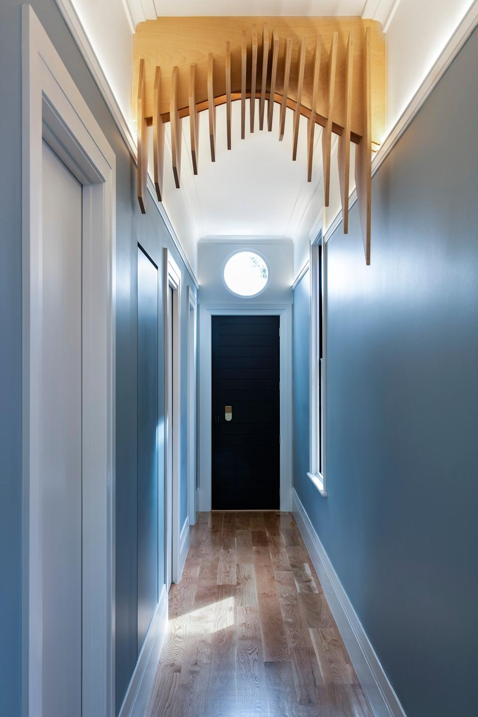 "<div class=""caption""> <strong>AFTER:</strong> The hallway is painted a light blue that continues into a front bedroom—this is where Nathan and Iman's families will stay when they come to visit. </div>"
